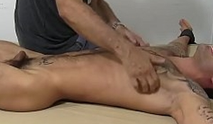 Bound tattooed hunk laughs his ass withdraw while dom tickles him